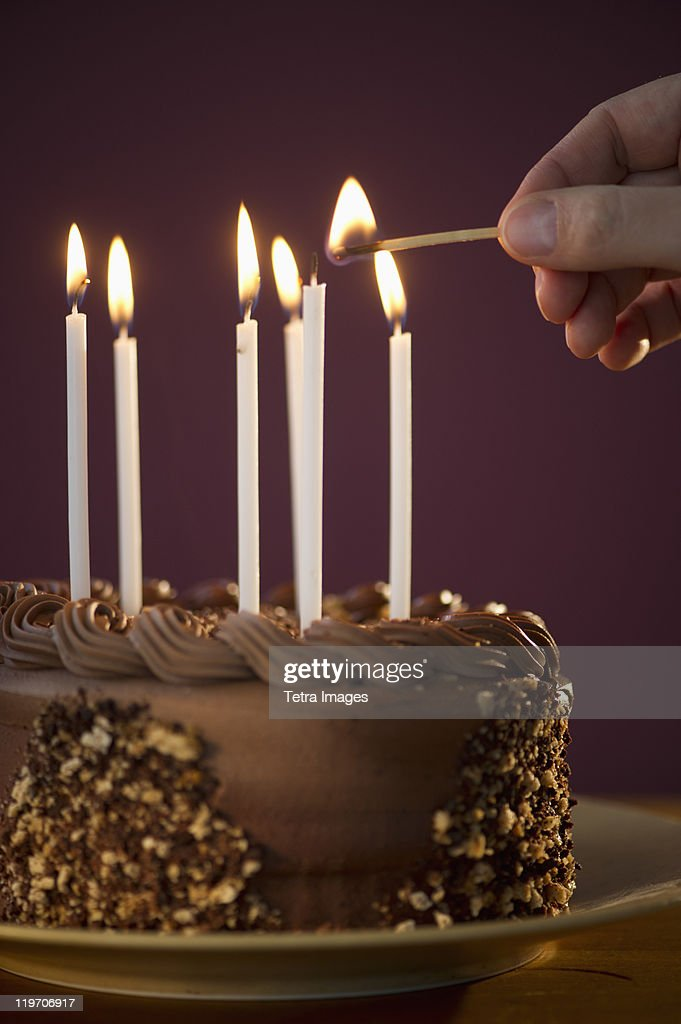Studio Shot Of Man Igniting Candles On Chocolate Birthday Cake Stock