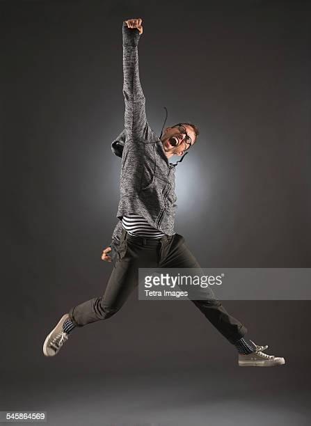 studio shot of man jumping - ガッツポーズ ストックフォトと画像
