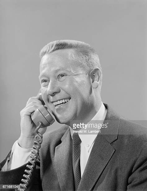 studio shot of man talking on phone - neckwear stock pictures, royalty-free photos & images