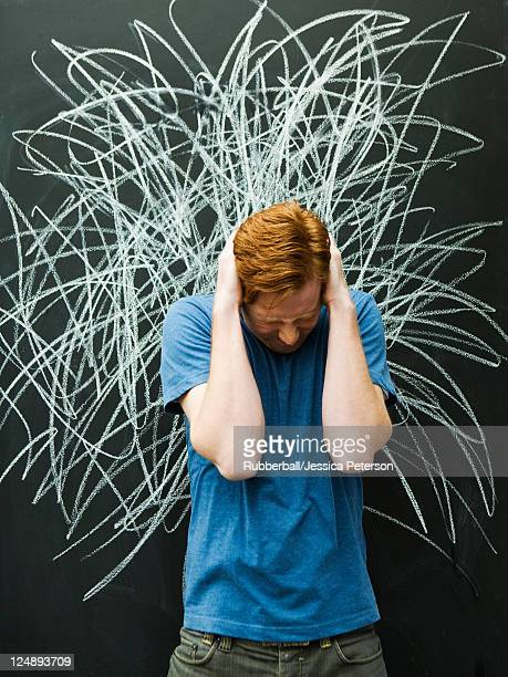 Studio shot of man with chalk scribble on blackboard