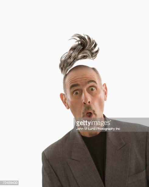 studio shot of man with toupee floating above head - homme chauve photos et images de collection