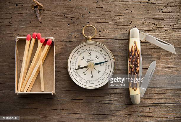 Studio Shot of matchsticks, compass and knife on wooden board