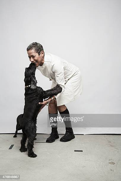 studio shot of mature woman having fun with pet dogs - older woman bending over stock pictures, royalty-free photos & images