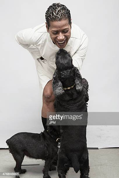 studio shot of mature woman playing with pet dogs - older woman bending over stock pictures, royalty-free photos & images