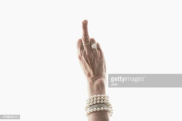 studio shot of mature woman's hand making obscene gesture - brazalete pulsera fotografías e imágenes de stock