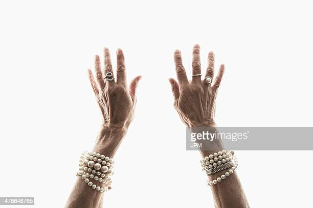 Studio shot of mature woman's reaching hands