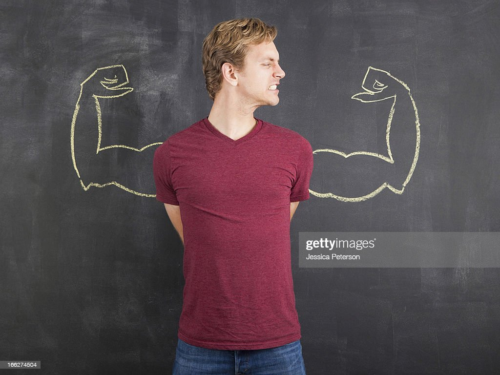 Studio shot of mid adult man with hands behind back and chalk drawing of artificial arms on blackboard : Stock Photo