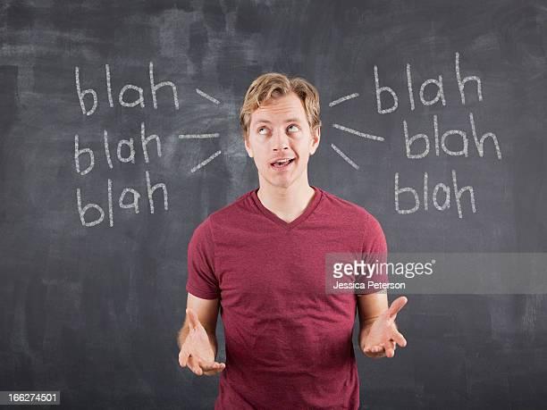 Studio shot of mid adult man with text on blackboard