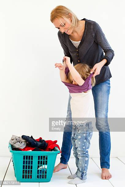 studio shot of mother taking off daughter's clothes for laundry - little girl taking off clothes stock photos and pictures