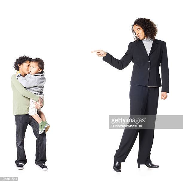 Studio shot of mother talking to sons (18-23 months, 8-9 years)