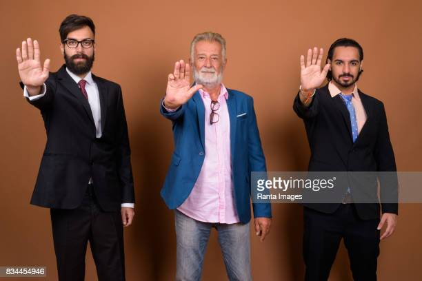 Studio shot of multi ethnic group of three bearded businessmen together against colored background