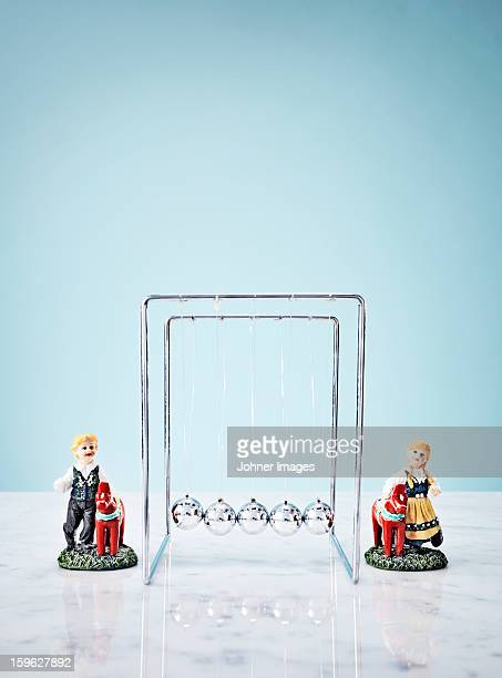 Studio shot of Newtons Cradle and small figurines