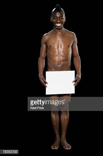 Studio Shot Of Nude African Man With Blank Paper In Front