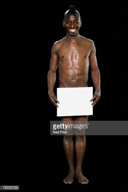 Studio shot of nude African man with blank paper in front of genital area