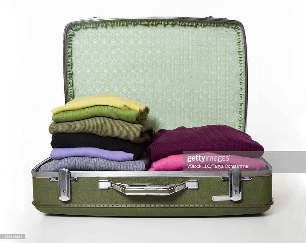 Studio shot of open suitcase full of clothing's : Stock Photo
