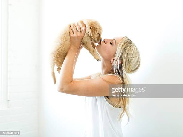 Studio shot of owner kissing Golden Retriever puppy