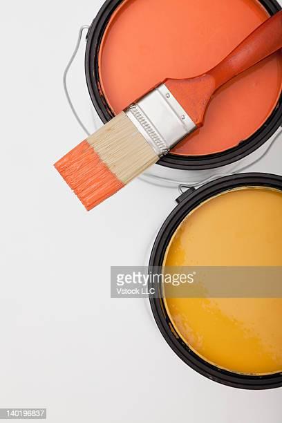Studio shot of paint brush on paint cans