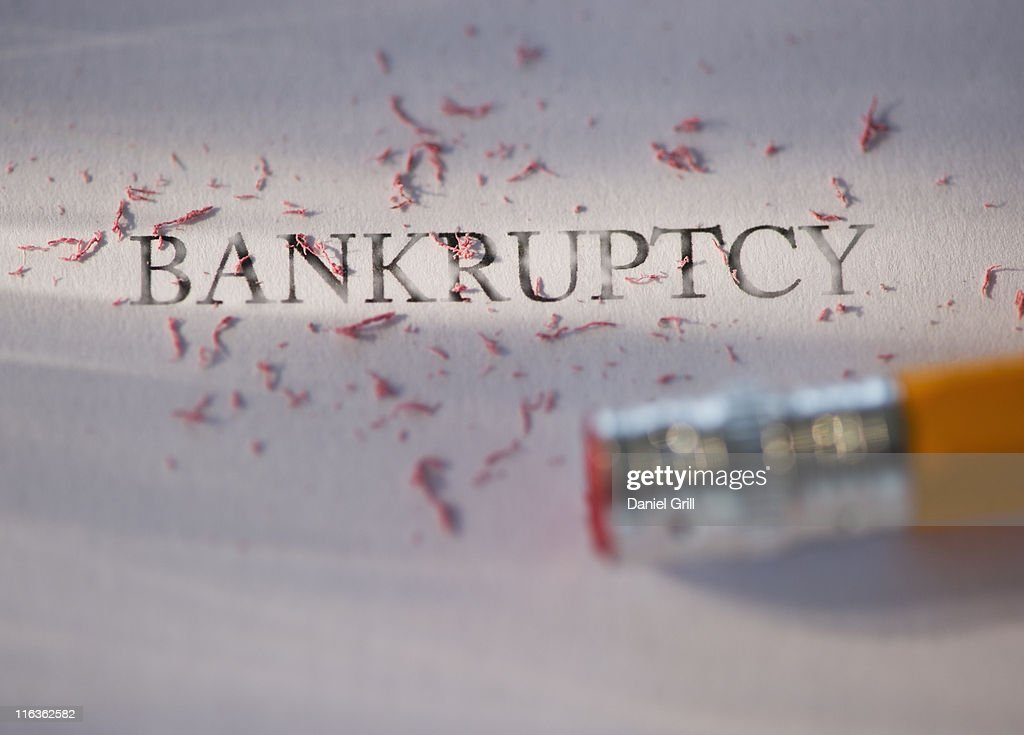 Studio shot of pencil erasing the word bankruptcy from piece of paper : Stock Photo