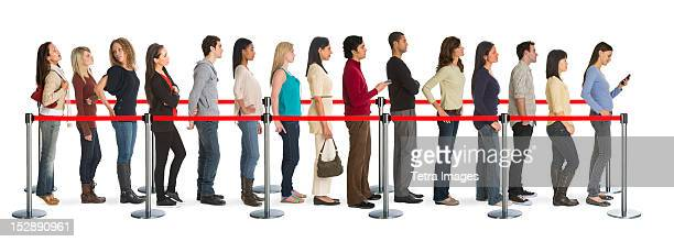 studio shot of people waiting in line - roped off stock photos and pictures