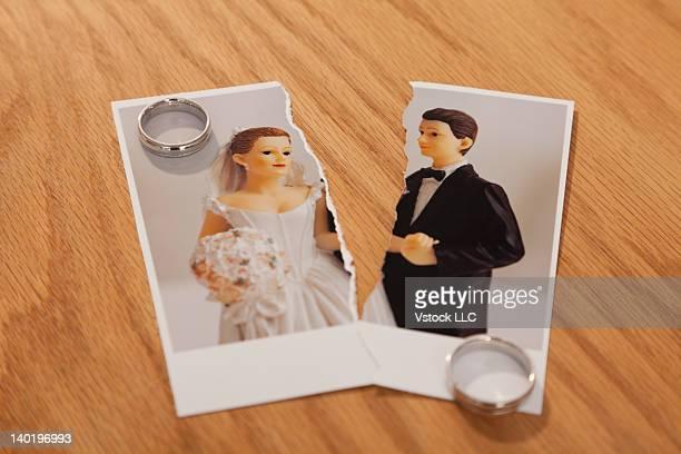 Studio shot of photo of bride and groom figurines torn in half and wedding rings