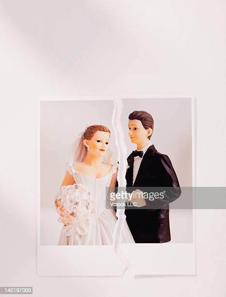 Studio shot of photo of bride and groom figurines torn in half