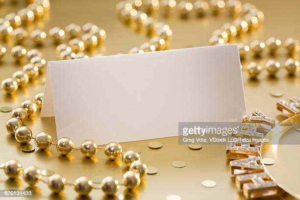 Studio shot of place card and decorations on golden background