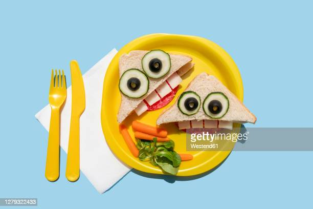 studio shot of plastic plate with two funny looking sandwiches withanthropomorphic faces - plastic plate stock pictures, royalty-free photos & images