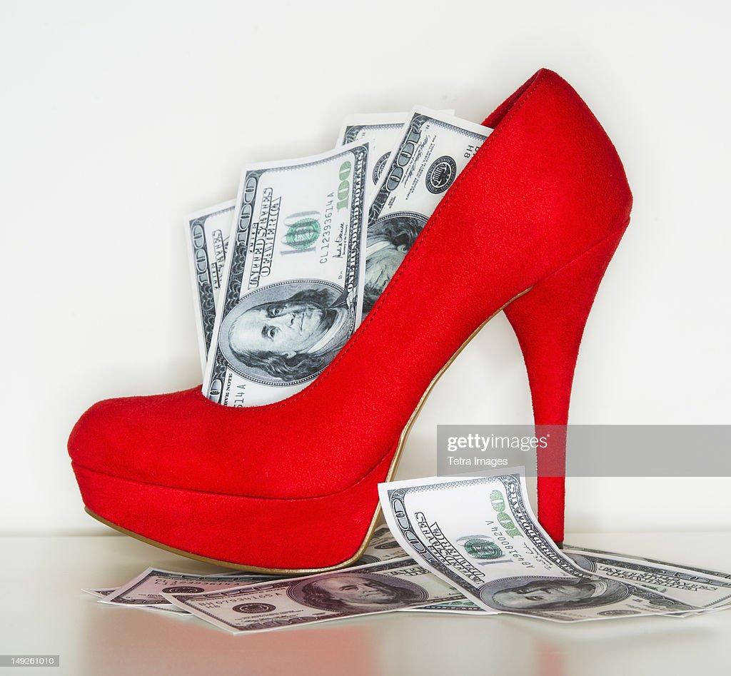 Studio shot of red stiletto and dollar bills : Stock Photo