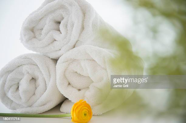 Studio Shot of rolled up towels with yellow flower