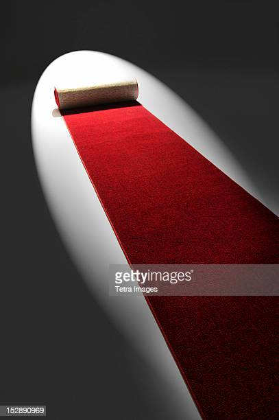 Studio shot of rolling out red carpet