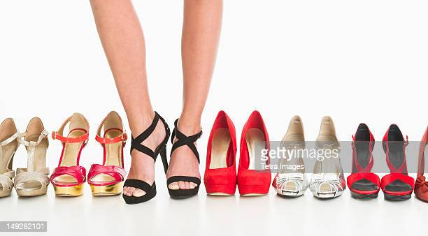 studio shot of row of shoes, woman wearing one of them - high heels stock pictures, royalty-free photos & images