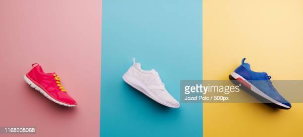 a studio shot of running shoes on bright color background flat lay - ténis calçado desportivo imagens e fotografias de stock