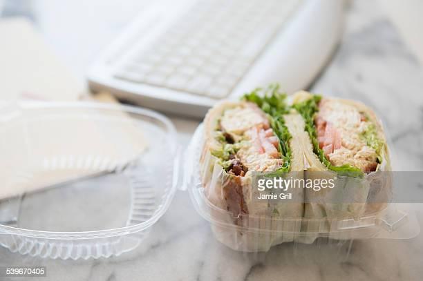 Studio shot of sandwich in box and computer keyboard