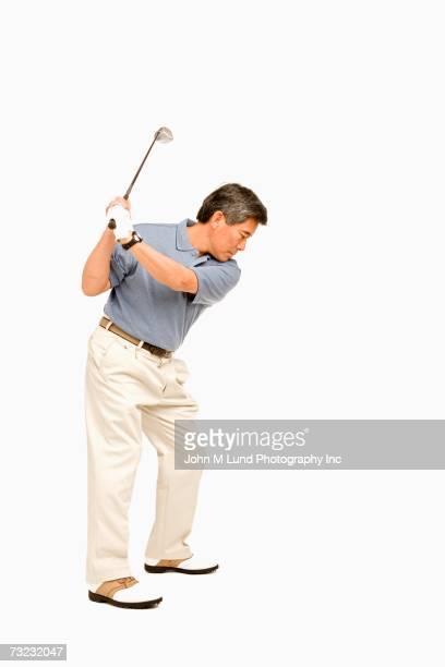 Studio shot of senior Asian man playing golf
