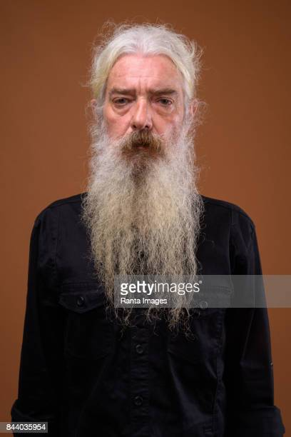 Studio shot of senior bearded man with hair tied back against colored background