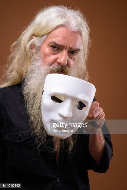 Studio shot of senior bearded man with white mask against colored background