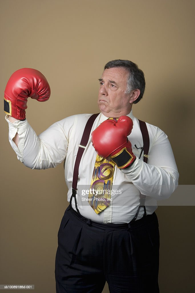 Studio shot of senior businessman wearing boxing gloves : Stockfoto