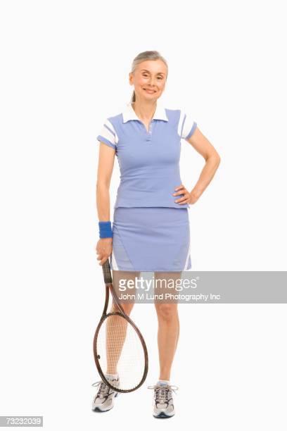 Studio shot of senior woman with tennis racket