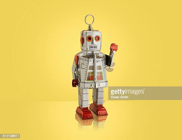 studio shot of silver robot with arm raised - toy stock pictures, royalty-free photos & images