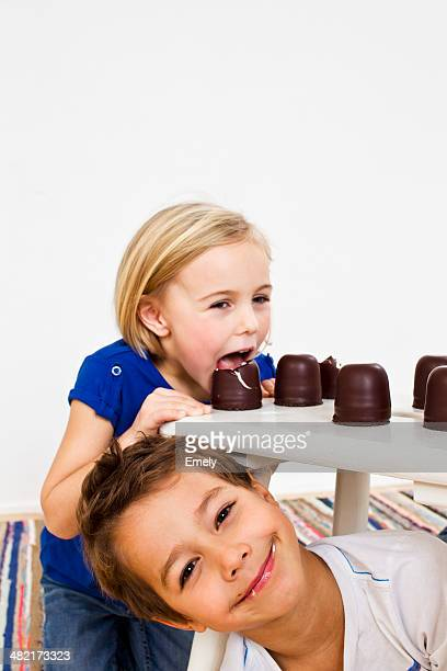 Studio shot of sister and brother with chocolate marshmallows