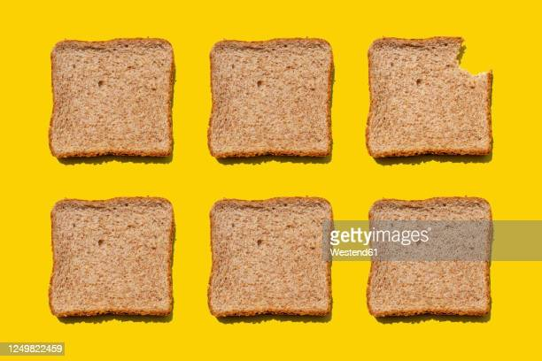 studio shot of six slices of wheat bread against yellow background - 噛む ストックフォトと画像