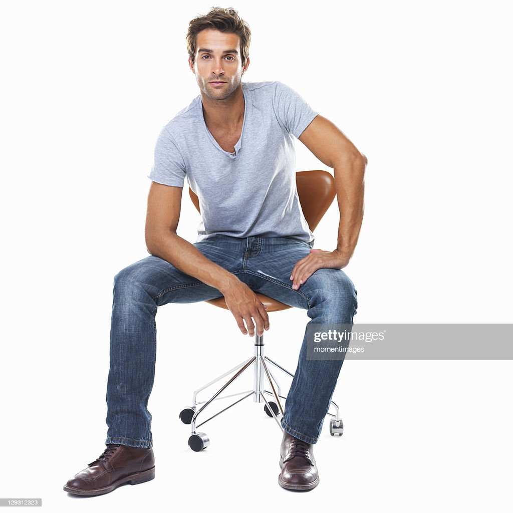 Sitting Chair: Studio Shot Of Smart Young Man Sitting On Chair Stock