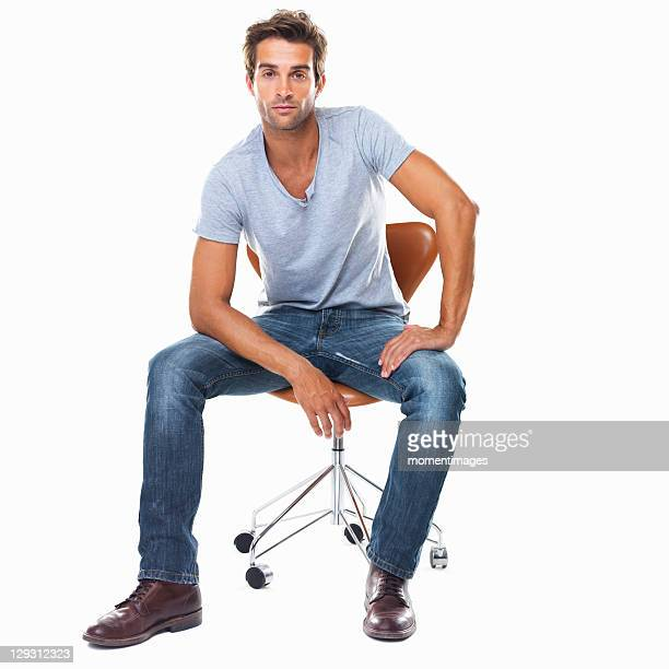 studio shot of smart young man sitting on chair - sitzen stock-fotos und bilder