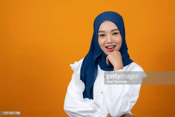 studio shot of  smiling muslim woman holding her chin with her hand, wearing headscarf in front of a light orange backdrop. - イラン文化 ストックフォトと画像