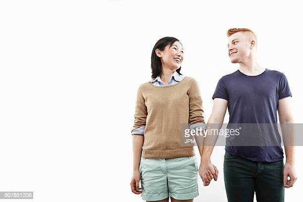 Studio shot of smiling young couple holding hands