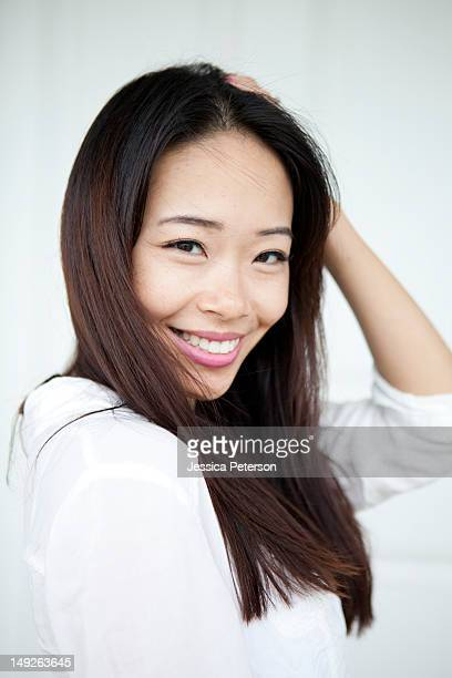 studio shot of smiling young woman - korean ethnicity stock pictures, royalty-free photos & images
