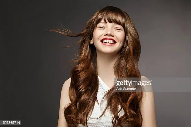 studio shot of smiling young woman - capelli mossi foto e immagini stock