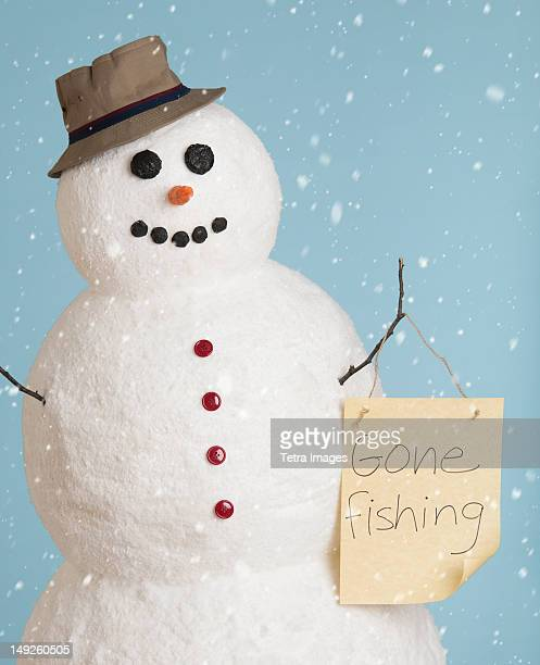 Studio shot of snowman dressed as fisherman