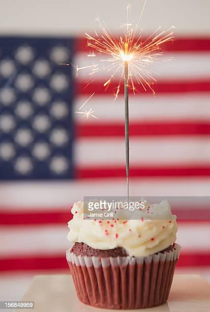 Studio shot of sparkler atop cupcake, american flag in background