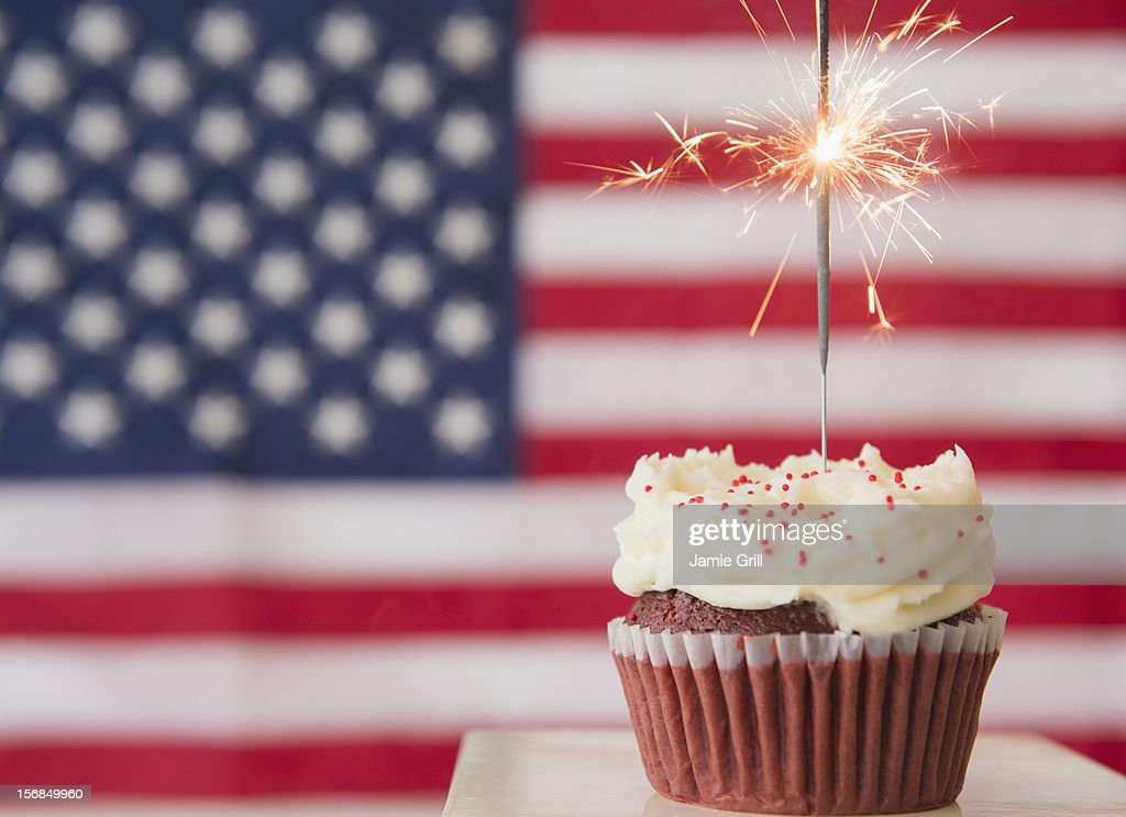 Studio shot of sparkler atop cupcake, american flag in background : Stock Photo